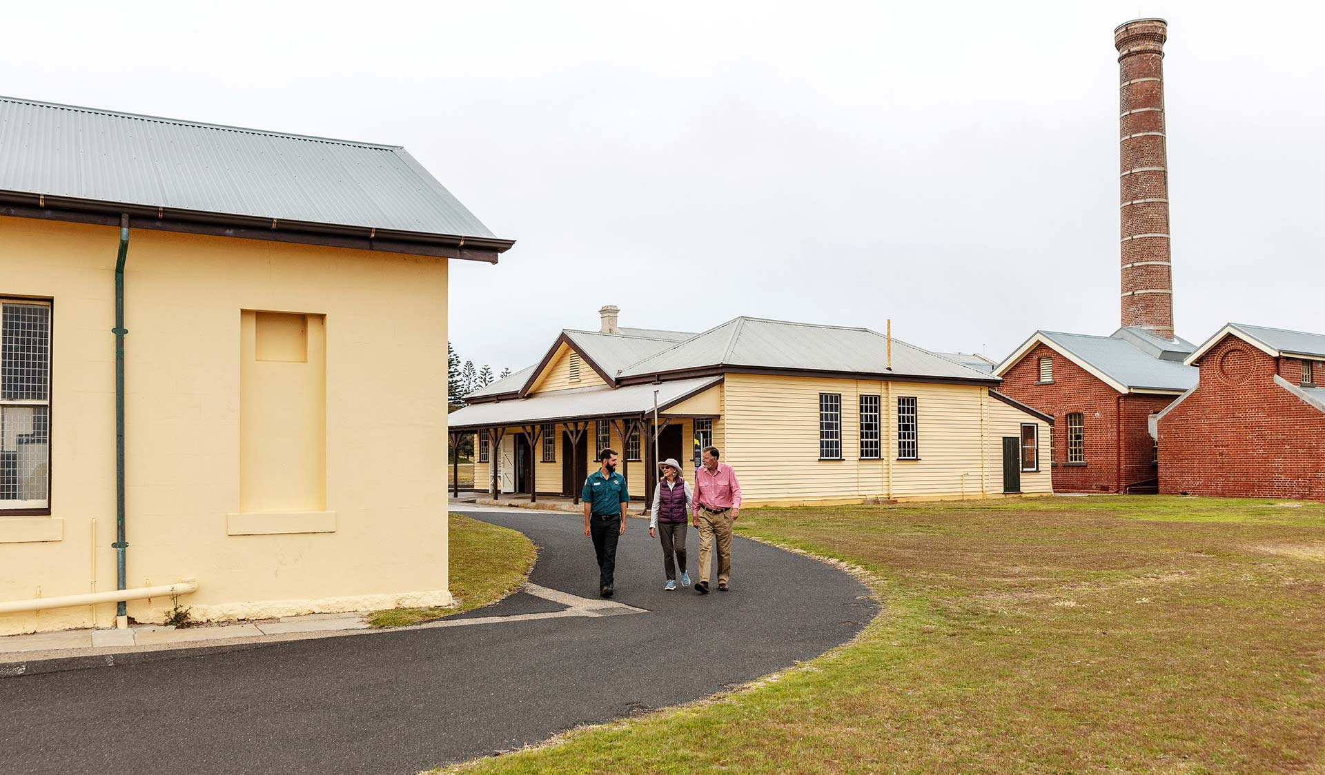 A retired couple walk with a ranger through the quarantine station at Point Nepean.