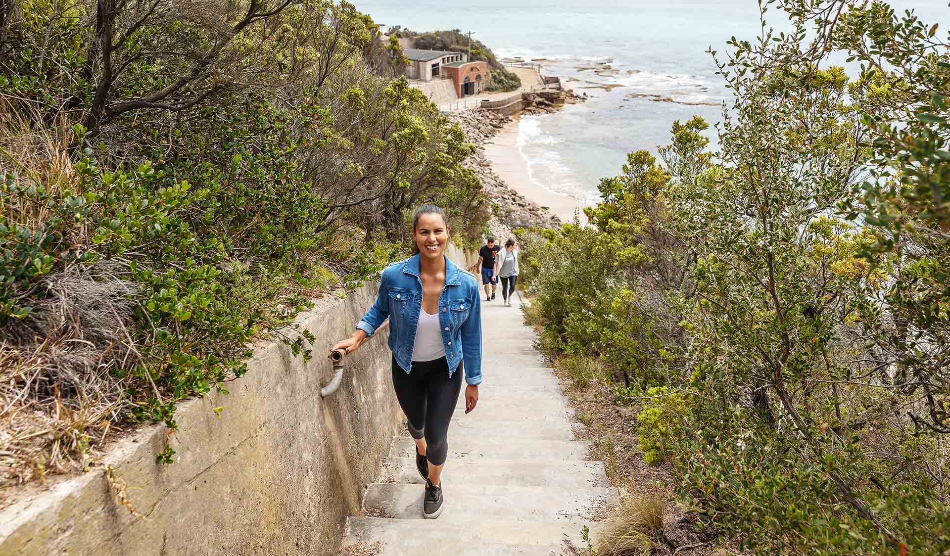 A women walks up the walkway from a beach at Point Nepean National Park.