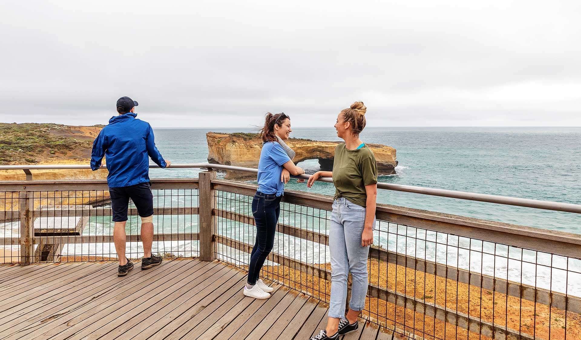 Two women in chat at lookout while a man takes in the view of London Bridge in the Port Campbell National Park.