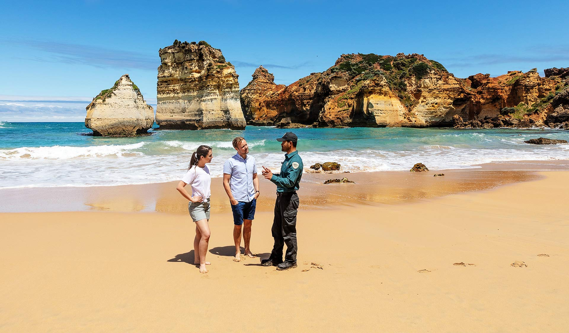 A couple talking to a Parks Victoria Ranger at Sandy Bay, Childers Cove