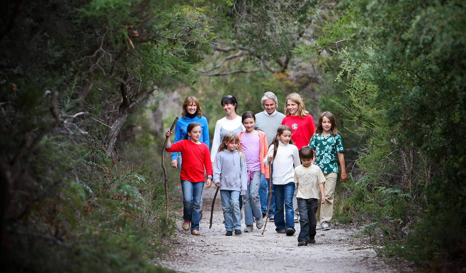 Two families walk along the Lilly Pilly Gully walk.