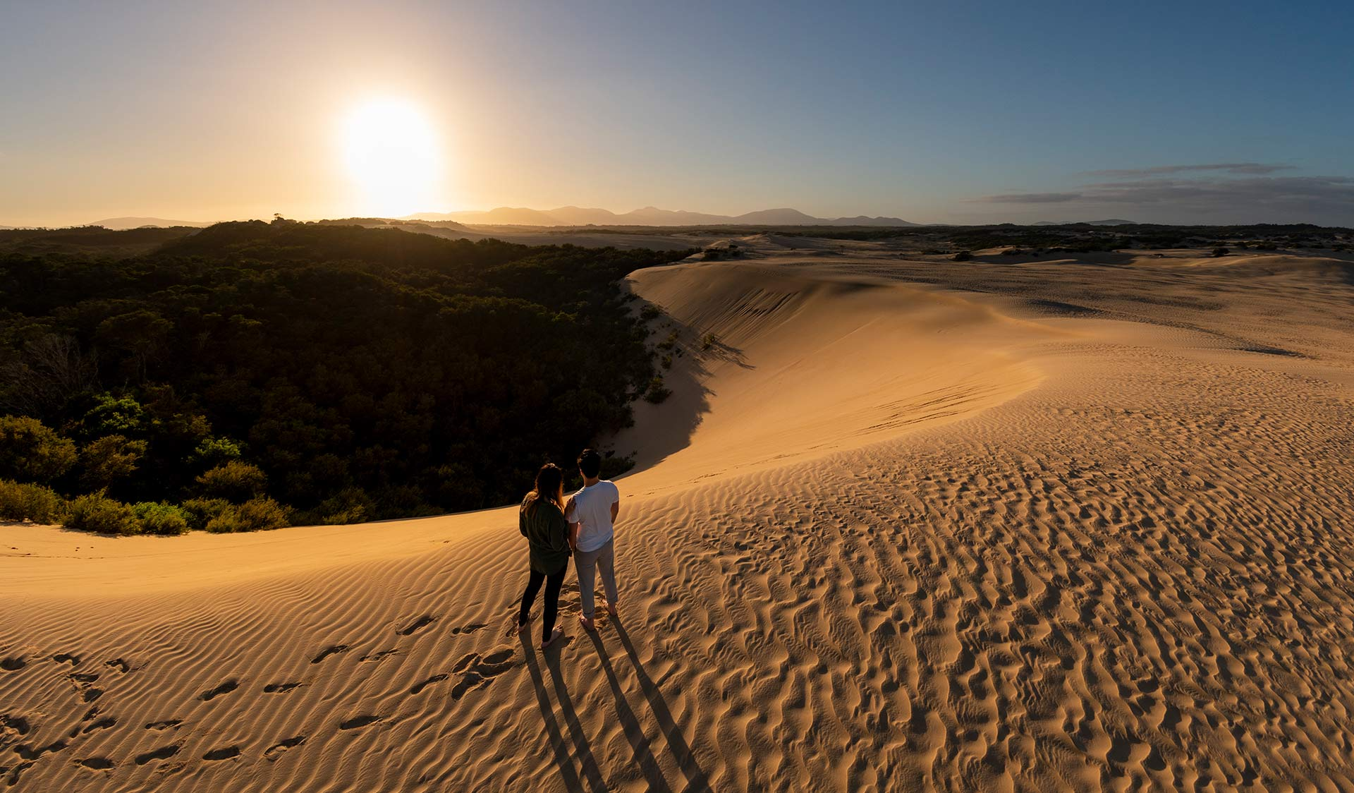 A man and woman rest and enjoy the view a the top of an enourmous sand dune in the northern part of Wilsons Promontory.