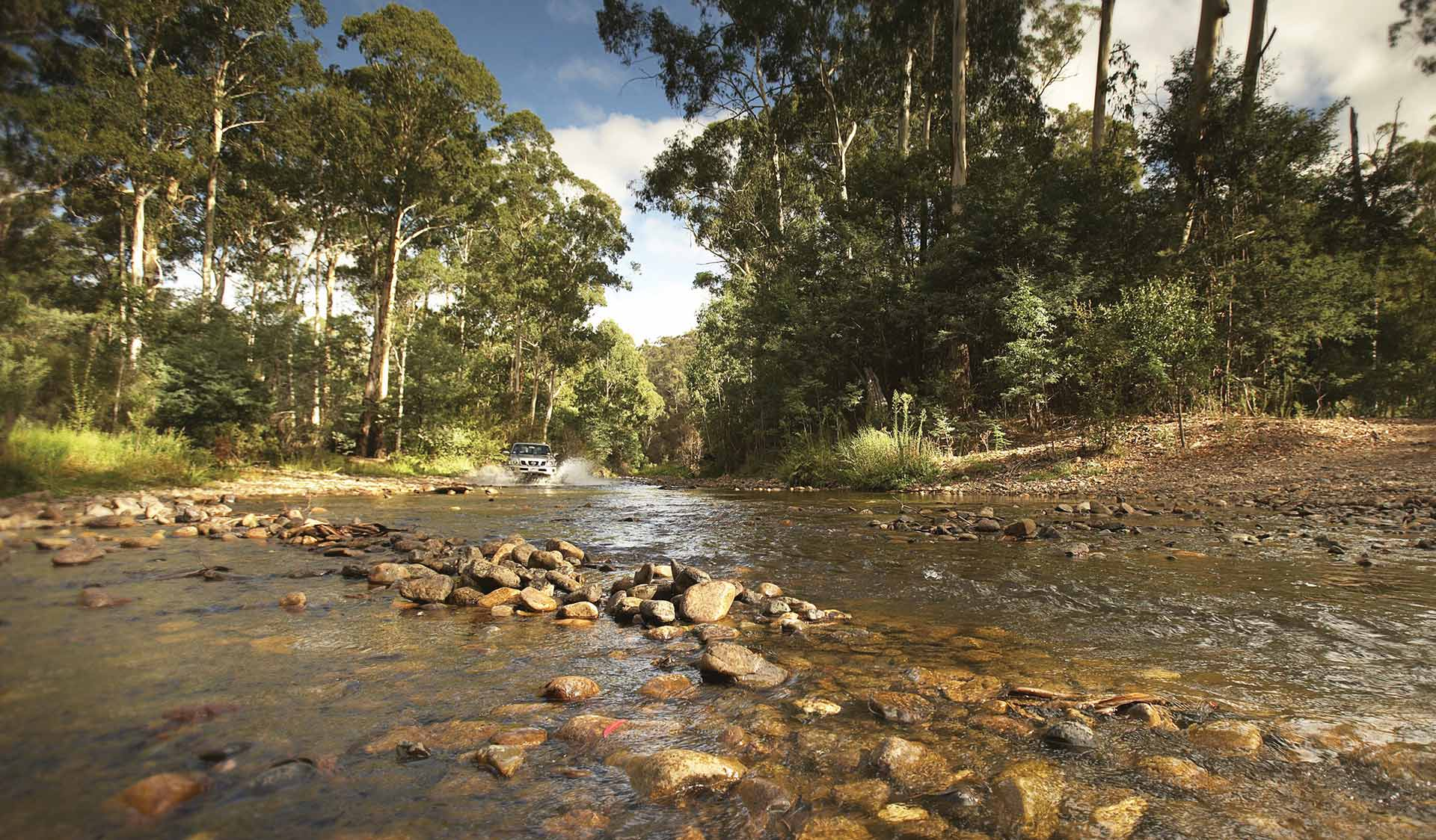 A four wheel drive crosses the Howqua River in the Alpine National Park.