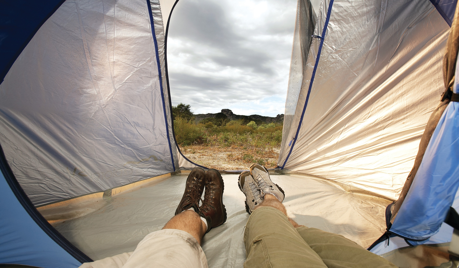 The view from inside a tent, looking out to the grassy landscape and cloudy sky.