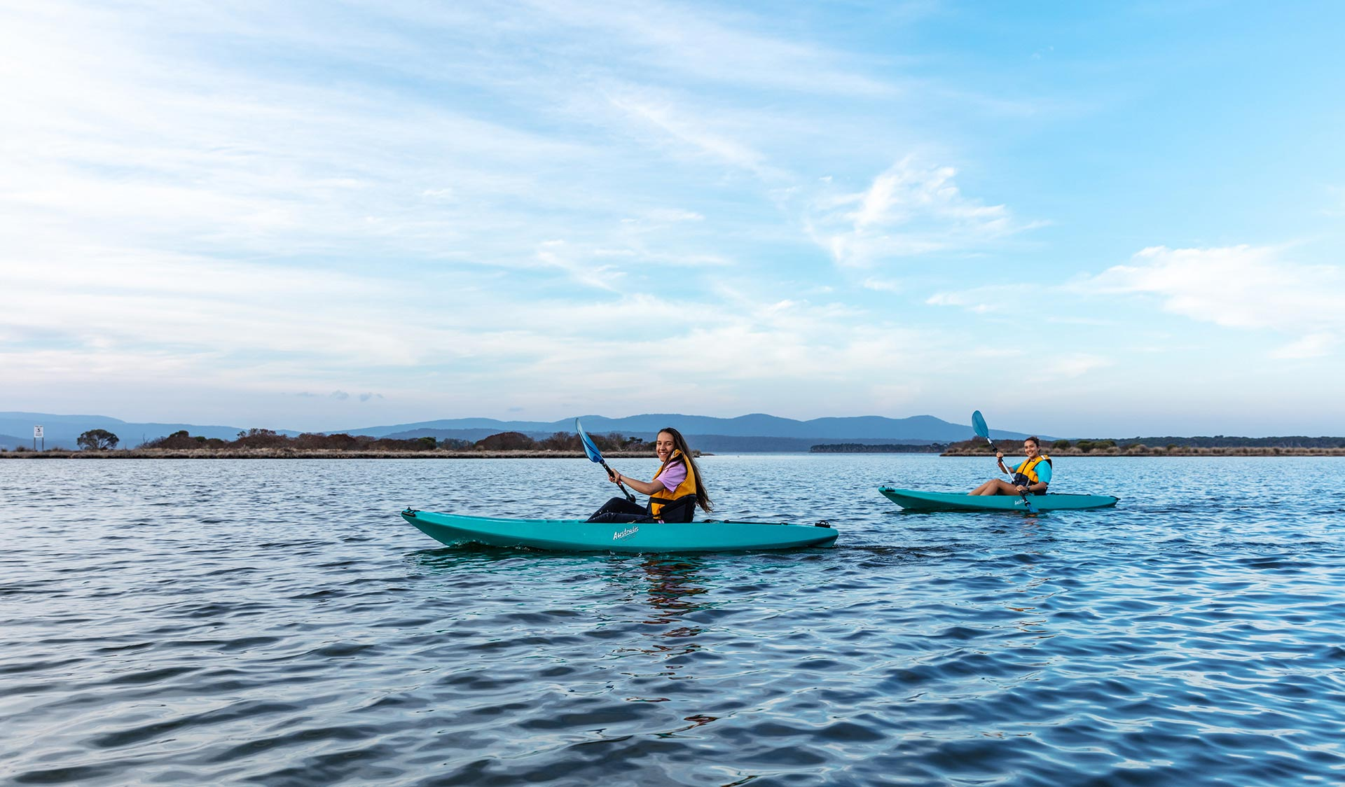 Two teenage girls kayaking on Mallacoota Inlet with mountains in the background.