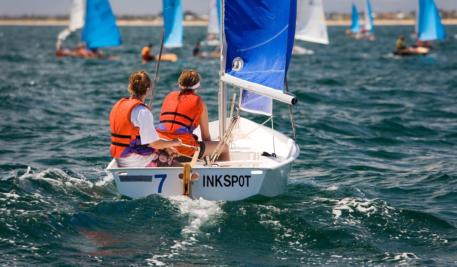 Two teenage girls take part in a sailing race on Port Philip Bay in a small boat called Inkspot.